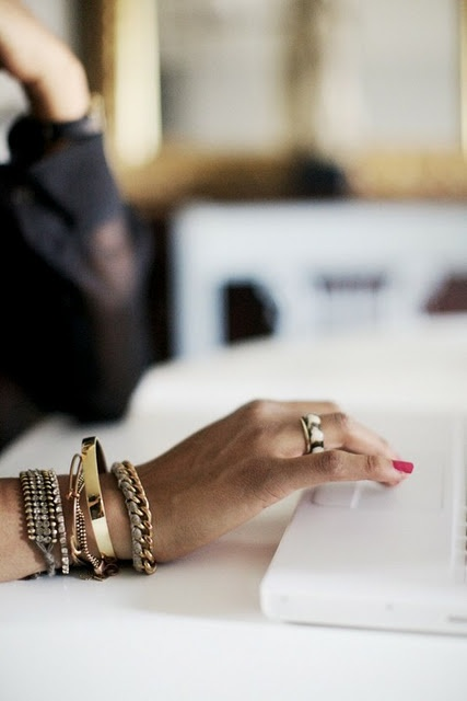 A picture of a woman working on her computer with mixed jewelry items.