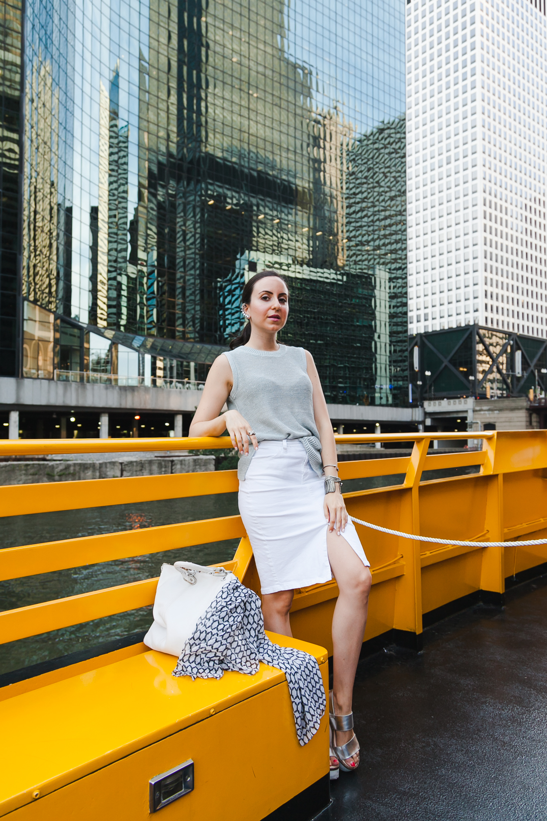 NoMad Luxuries wearing a white denim skirt and a blue linen top in Chicago on the water taxi in the Summer