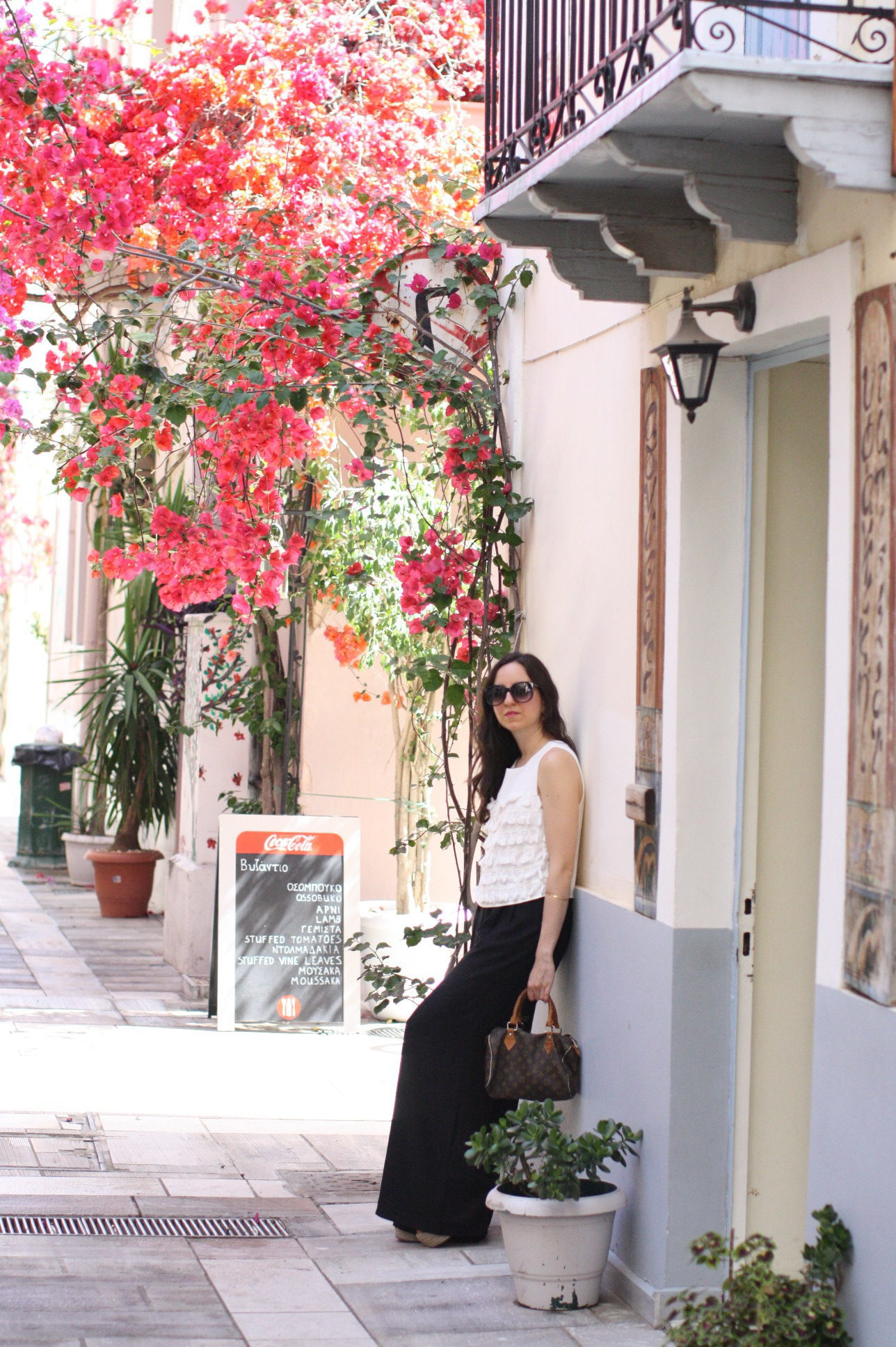 Yana Puaca of NoMad Luxuries wearing a white tassel top and black palazzo pants with asos flatform shoes and a louis vuitton purse and vintage gold jewelry