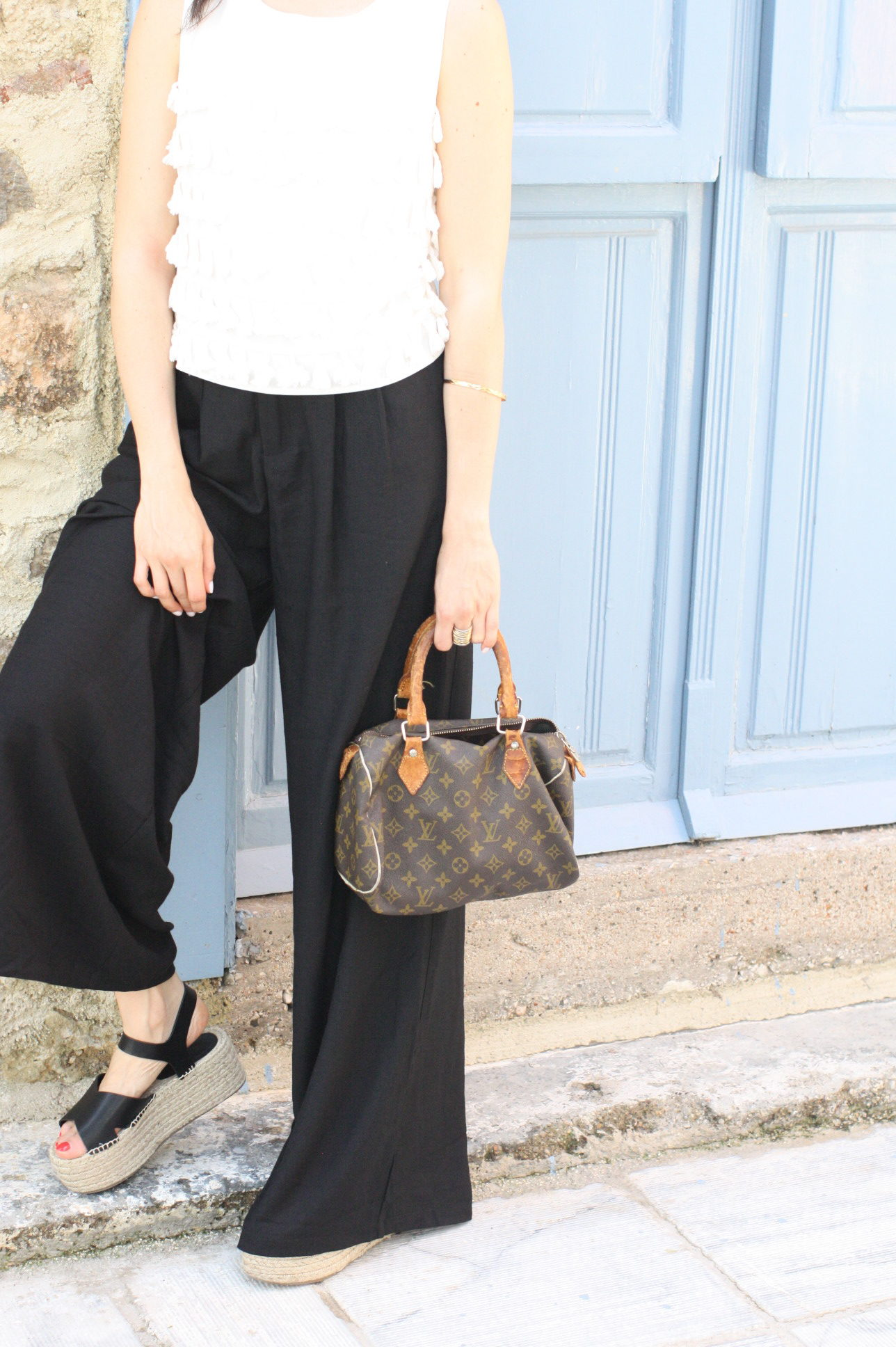 Yana Puaca of NoMad Luxuries wearing a white tassel top and black palazzo pants with asos flatform shoes and a louis vuitton purse