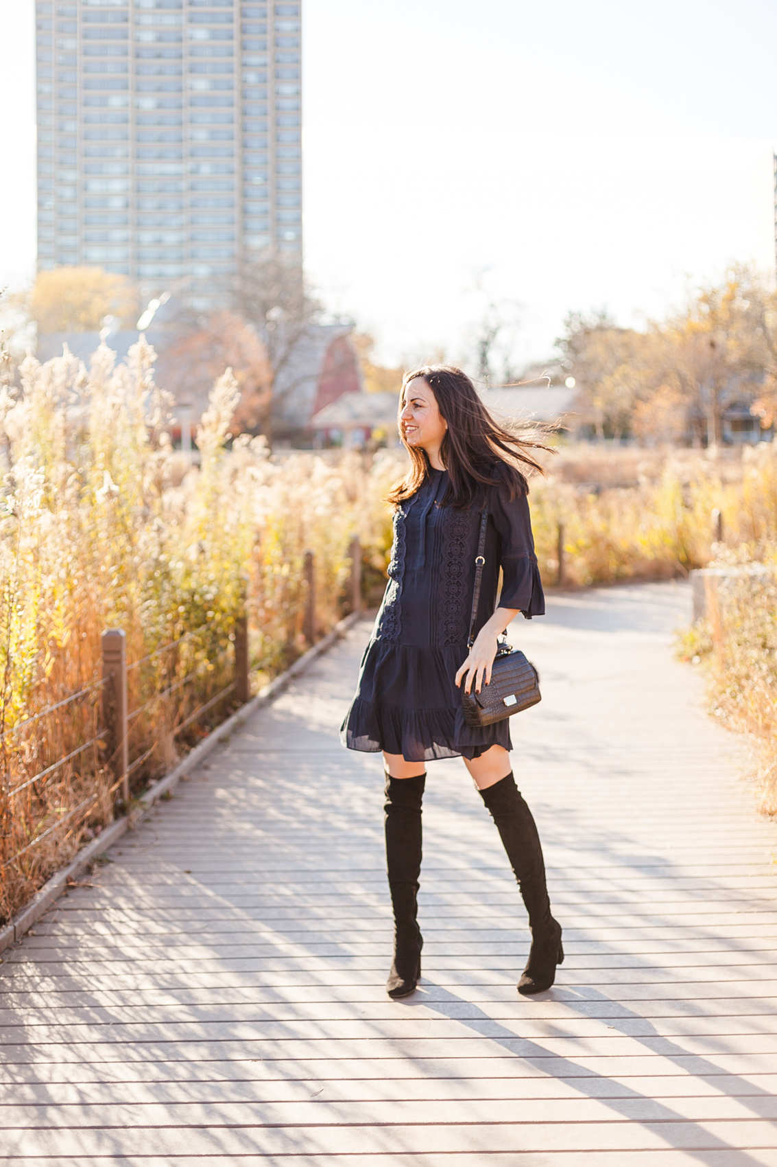 Yana Frigelis of NoMad Luxuries wearing a navy boho inspired dress from loft and over the knee boots for fall in chicago