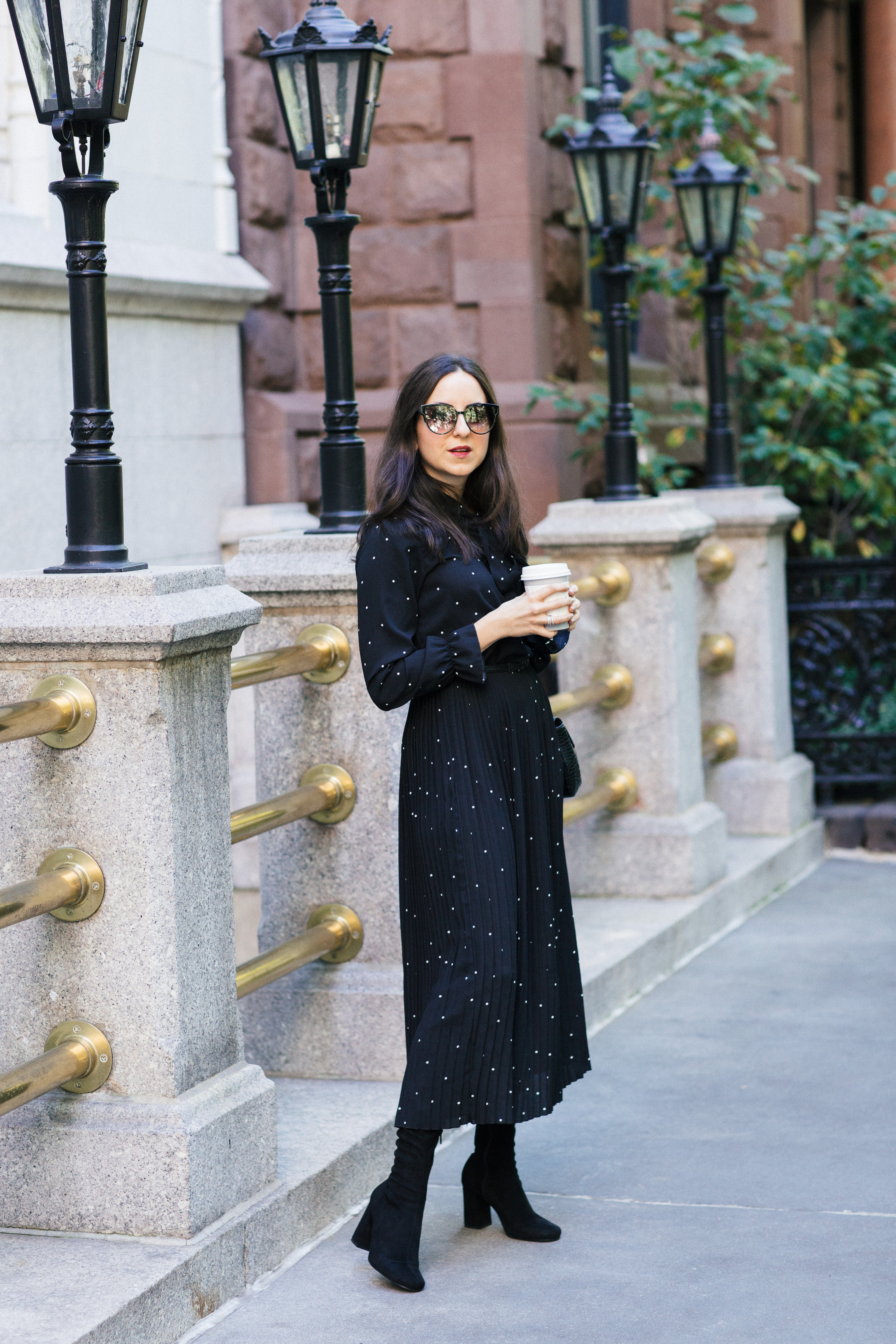 Yana Frigelis of NoMad Luxuries wearing a black polka dot dress from Romwe for the fall in Gramercy Park New York