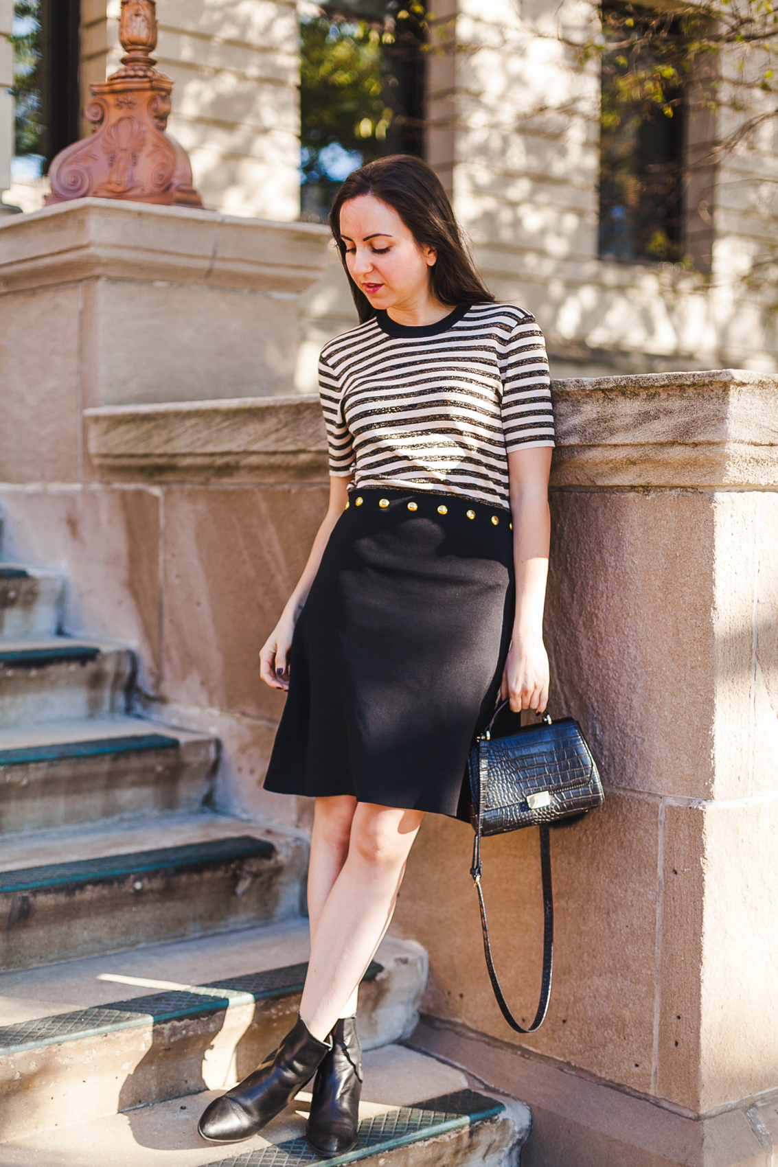 Yana Frigelis of NoMad Luxuries wearing a Sandro striped dress in black and gold in Chicago