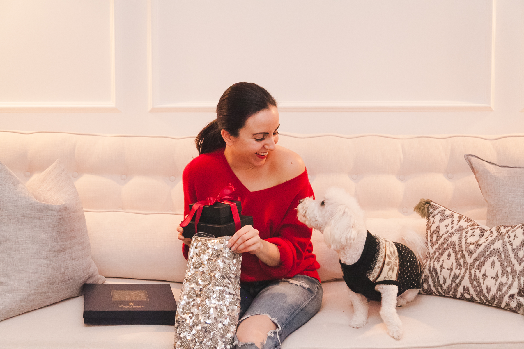 Yana Frigelis of NoMad Luxuries wearing a red cashmere sweater and decorating the Christmas tree for the holidays at home