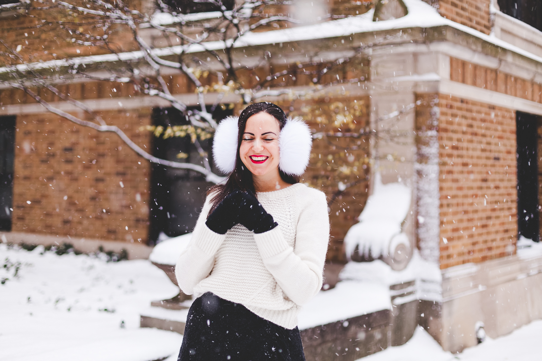 Yana Frigelis of NoMad Luxuries wearing fur earmuffs and a cozy cableknit sweater in the snow for the holidays