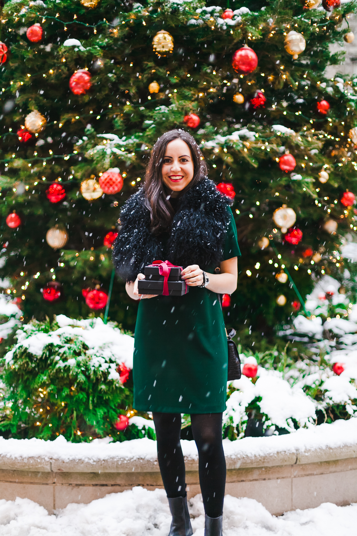 Yana Frigelis of NoMad Luxuries wears a green cocktail dress from zara and a fur scarf from asos for the holidays