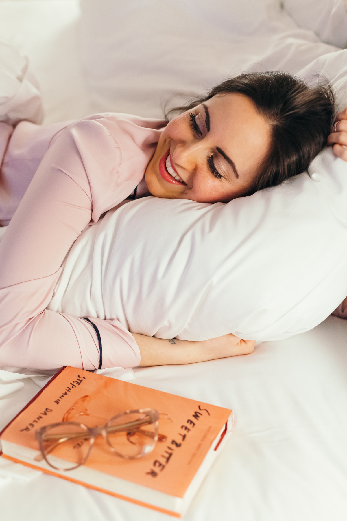Yana Frigelis of NoMad Luxuries wearing a mango pink silk pajama blouse in bed