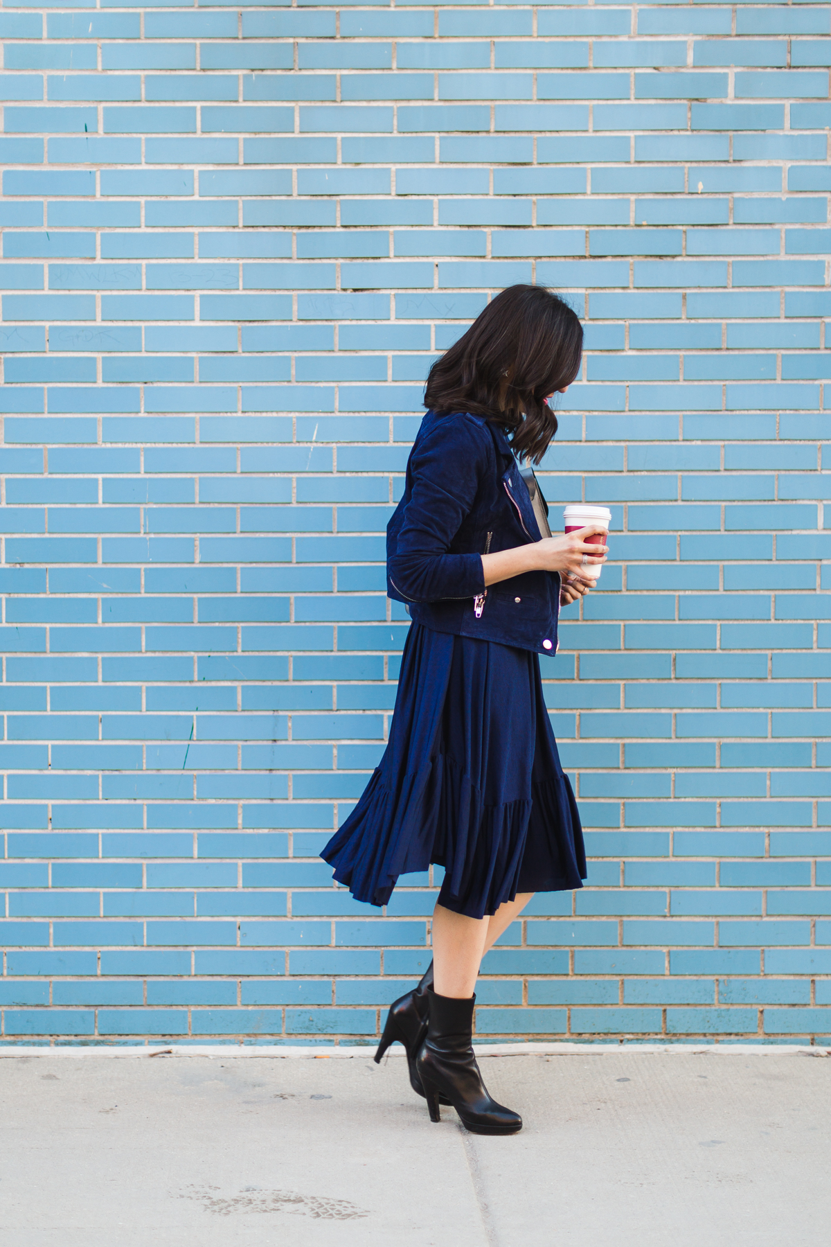 Yana Frigelis of NoMad Luxuries wearing a navy zara pleated dress with a navy moto jacket from tj maxx for spring