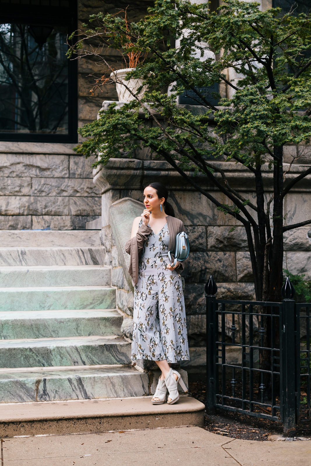 Yana Frigelis of NoMad Luxuries wearing a floral culotte jumpsuit in nuetral colors and accessories for Spring