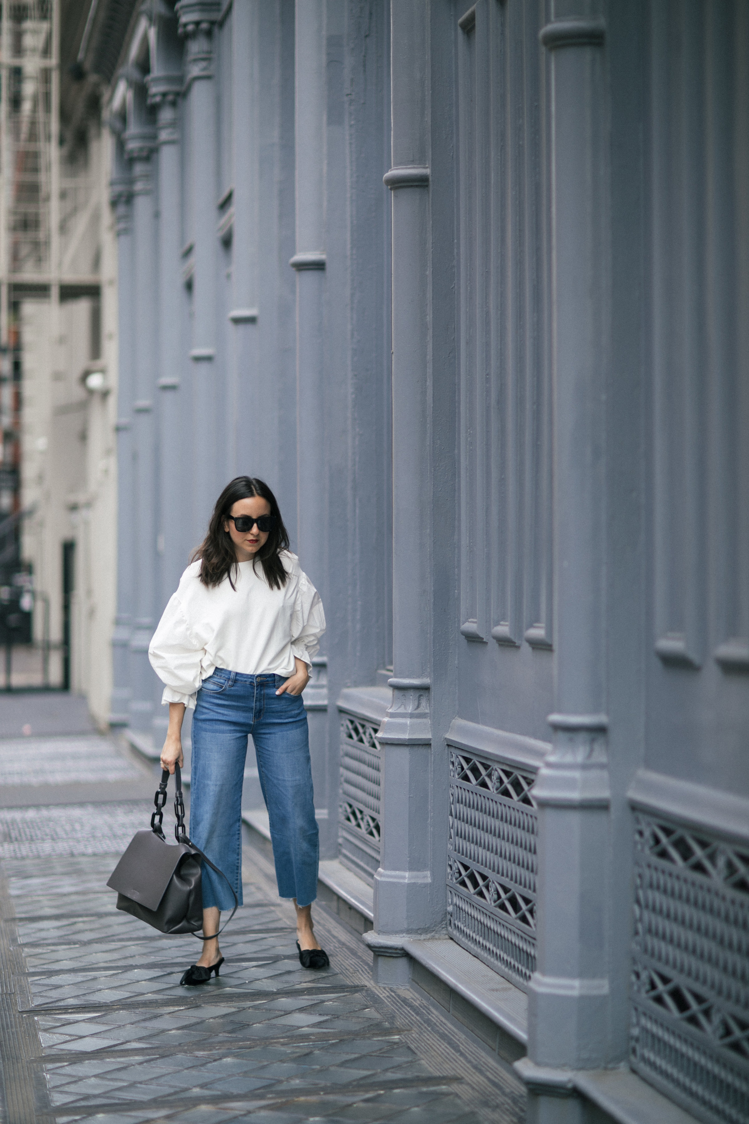 Yana Frigelis of NoMad Luxuries showing how to style a casual denim look with a sweatshirt with statement sleeves from mango and velvet, bow mules for Fall