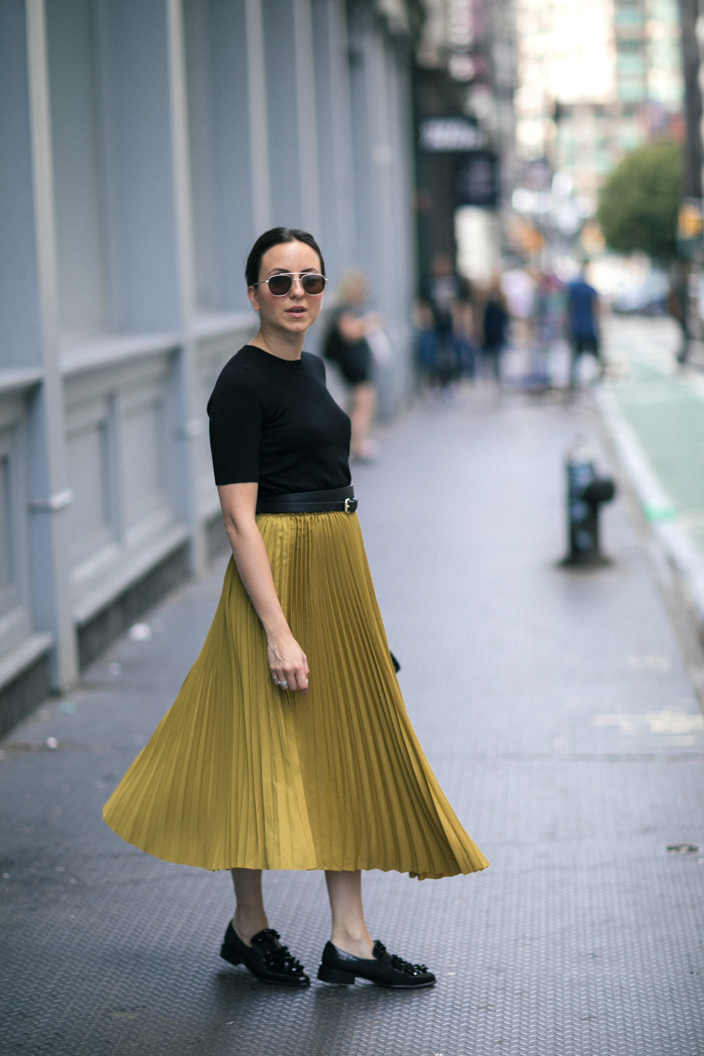 Yana Frigelis of NoMad Luxuries wearing a midi skirt from Zara for a fall trend and loafers for a casual look in new york