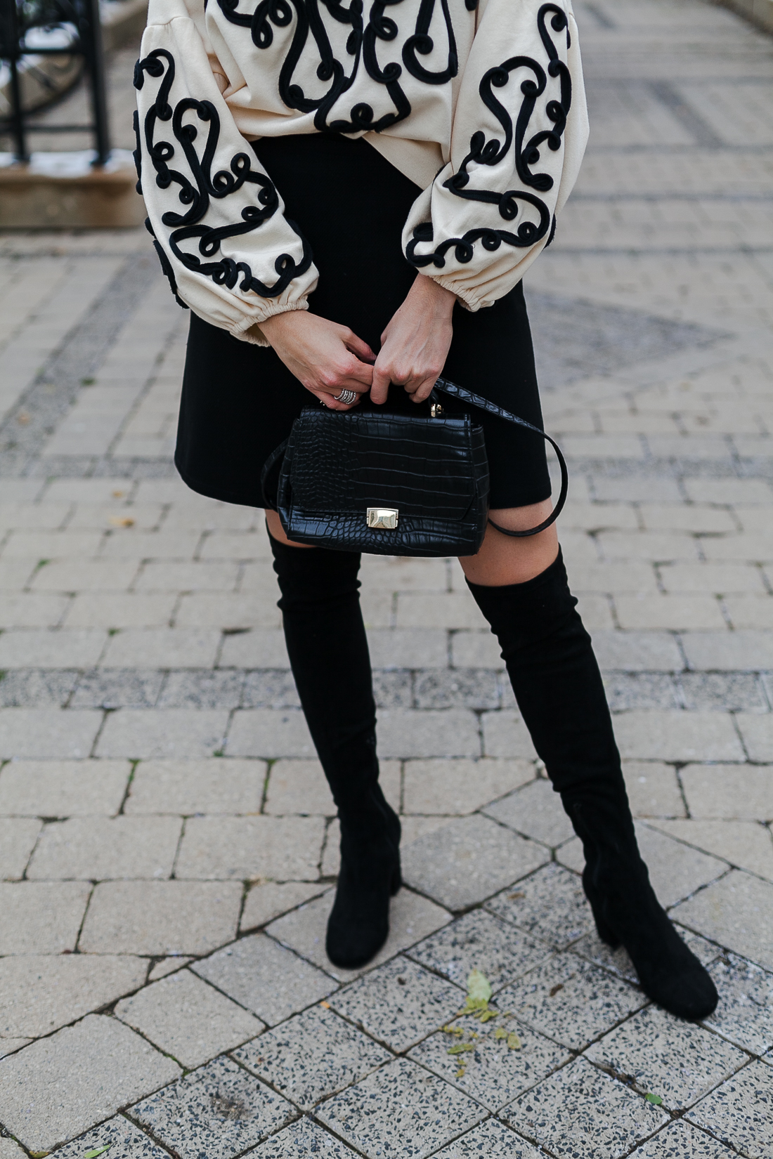 Yana Frigelis of NoMad Luxuries wearing an embroidered sweatshirt from zara and over the knee boots for a simple yet statement making outfit