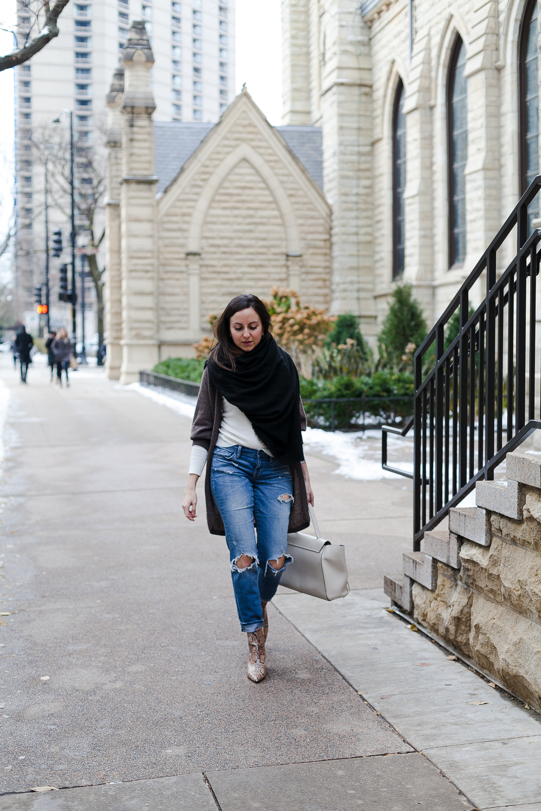 Yana Frigelis of NoMad Luxuries wearing a neutral look with ripped jeans and snake skin booties for Fall in Chicago