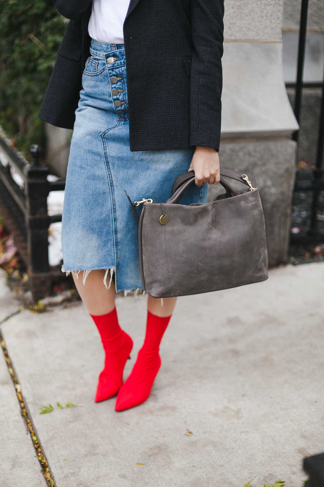 Yana Frigelis of NoMad Luxuries wearing a graphic tee under a blazer with red sock boots and a jean retro skirt for Fall