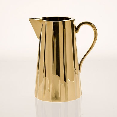 A brass milk pitcher to serve alongside a tea party.