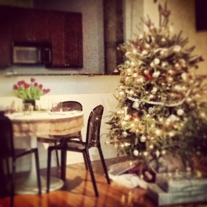 Nomad Luxuries; monochromatically decorated christmas tree towering in the living room.