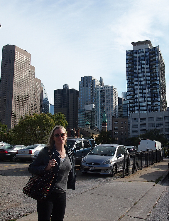Nomad Luxuries photo of Claire with Chicago buildings on a bright day.