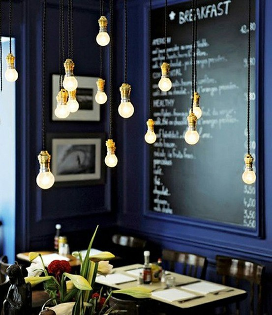 Nomad Luxuries image of interior of navy walls and gold hanging light fixtures.