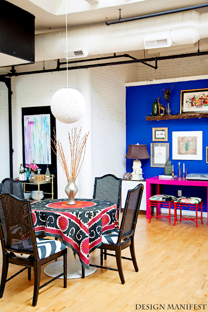 Nomad Luxuries photo of modern industrial interior with exposed vents and pops of color.
