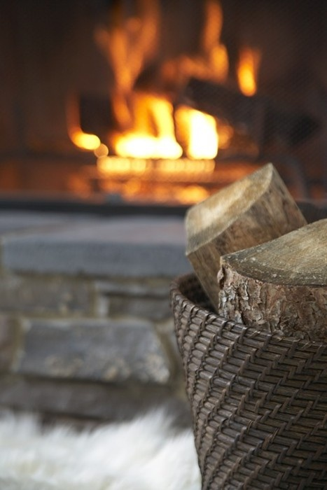 Nomad Luxuries displaying fireplace with wood for a fall ambiance