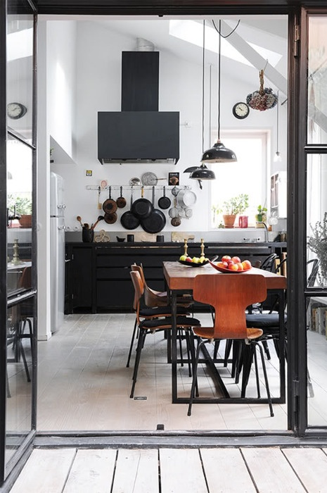 Nomad Luxuries image of industrial black and white kitchen with wood detailing.