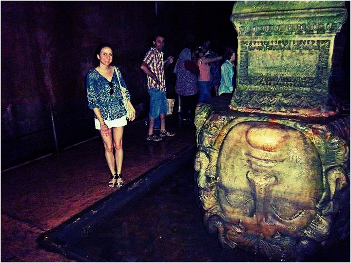 Nomad Luxuries photo of Yana in front of Medusa's stone sculpture.