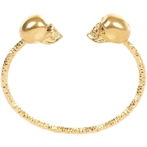 Nomad Luxuries image of gold skull bracelet as an accessory for oxblood attire.