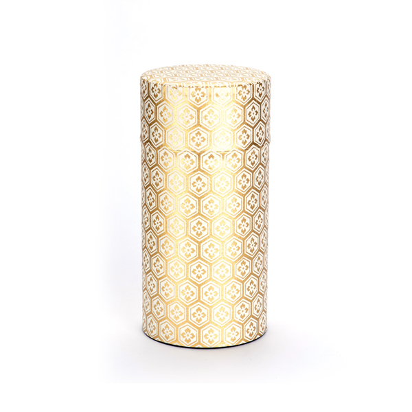 A luxuriously decorated gold tea canister with gold foil detailing.