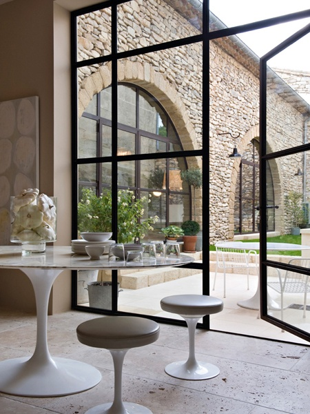 Nomad Luxuries image of dining room area leading into outdoor space focusing on Tuscany windows.