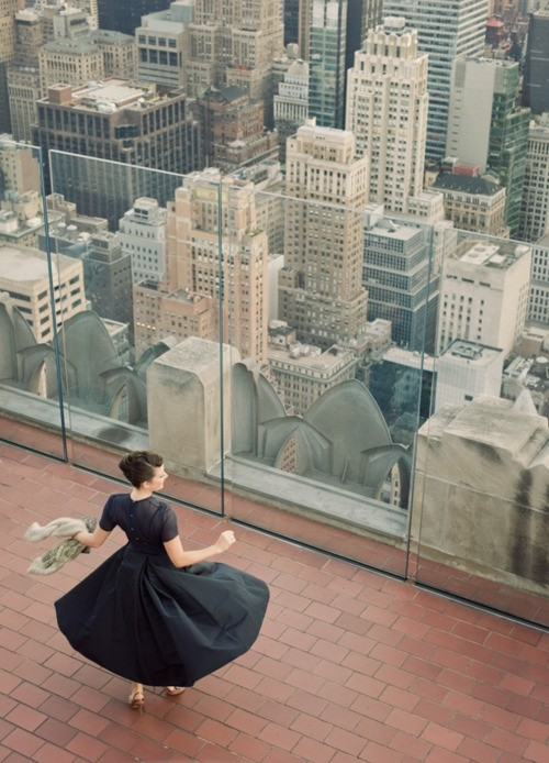 Nomad Luxuries photo of a woman standing on a balcony peering down at buildings in New York.